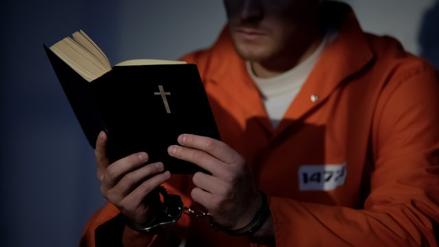 Imprisoned man in handcuffs reading bible, feeling guilty and praying for soul