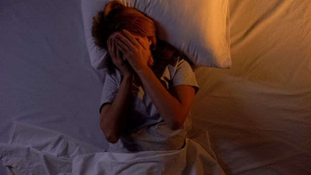 Woman hiding face while lying in bed, cant wake up in morning, tedious sleep