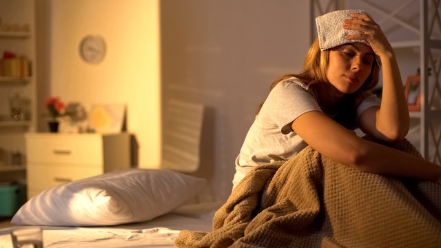 Sick lady with towel on forehead suffering from migraine, sitting in bed at home