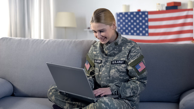 Cheerful american soldier woman making videocall on laptop pc at home, military