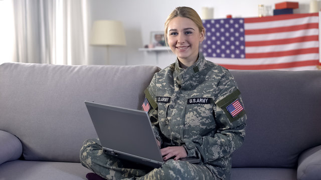 Kind american soldier woman typing on laptop and looking at camera, volunteer