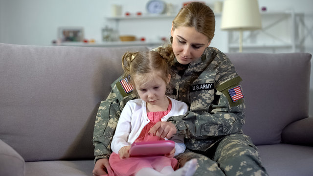 Military mother teaching little girl playing on toy tablet, educational gadget