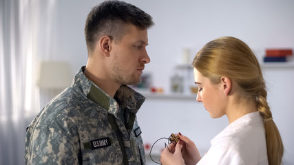 Upset woman giving wooden cross necklace on male soldier, emotional farewell
