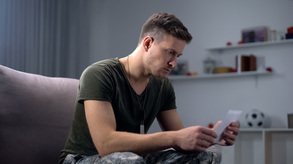 Disappointed soldier looking at family photo, relationship problem, break-up