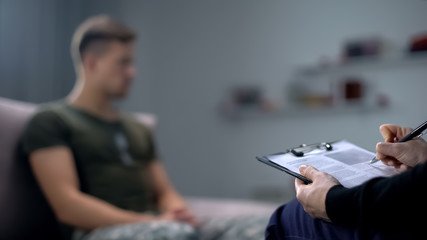 Psychologist making notes during therapy session with sad male soldier, PTSD Wall mural