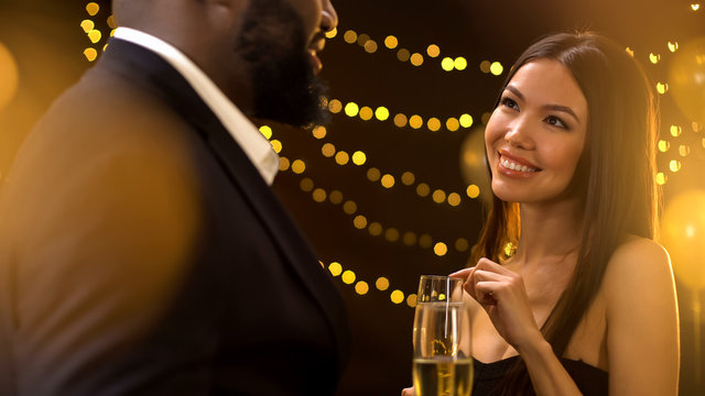 Beautiful asian woman flirting with man at party, holding champagne glasses