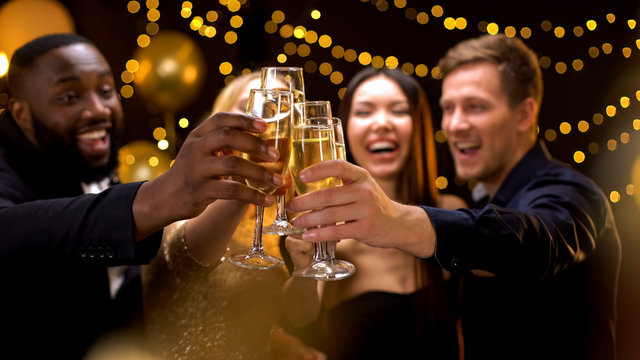 Cheerful multi-racial friends clinking champagne glasses, corporate event, fun