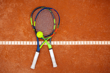 Top view of two tennis rackets and yellow tennis ball lie on the clay court.