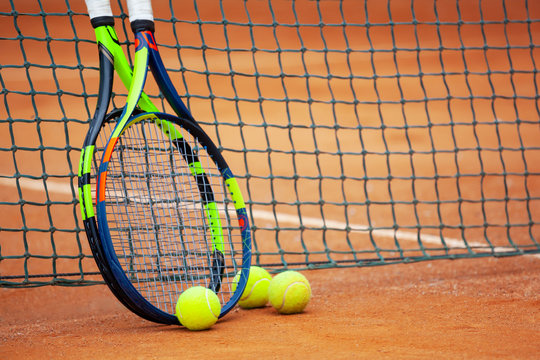 Tennis rackets and balls leaned against the net.