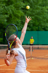 Young female tennis player serving.