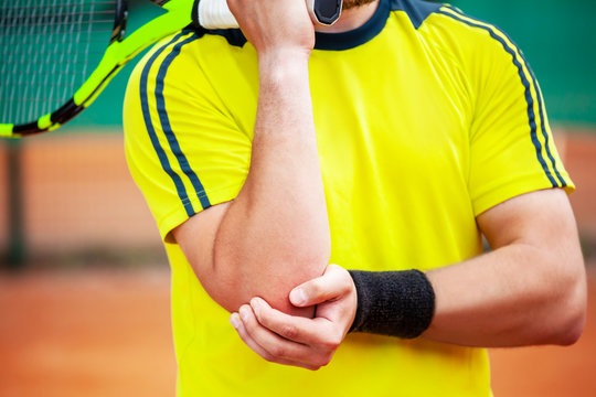 Male tennis player holding his injured elbow.
