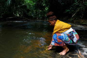 A member of a heritage tour group says a prayer to her enslaved ancestors at the Assin Manso river