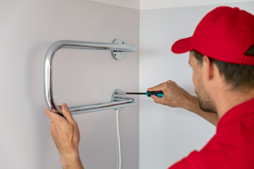 worker installing electric towel dryer on the bathroom wall