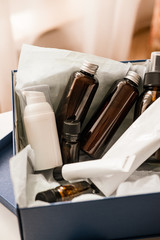 Beauty box set, brown bottles and white tubes of natural cosmetics. Blogger skincare, face, hair and body essentials, salon treatments. Overhead, minimalism package, branding mockup. No text