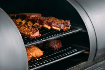 Professional kitchen appliance. Poultry, beef and pork meat, ribs cooked in BBQ smoker. Wall mural