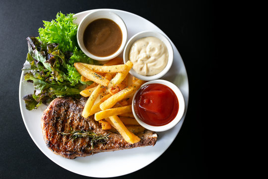 Grilled meat, Porkchops steak with pepper sauce and salad.