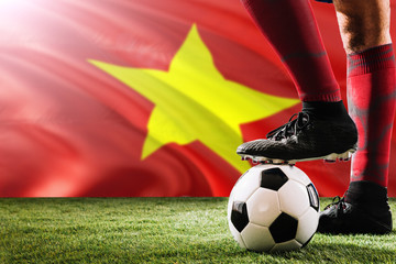 Close up legs of Vietnam football team player in red socks, shoes on soccer ball at the free kick or penalty spot playing on grass.