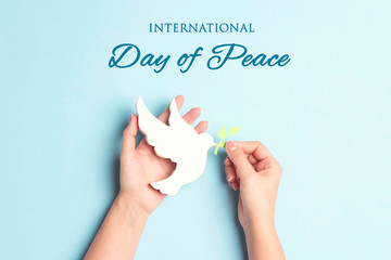 World Peace Day greeting card. Female hands hold dove of peace with olive branch.