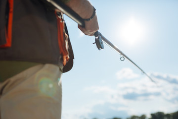 Close up of man holding fishing tackle while catching fish