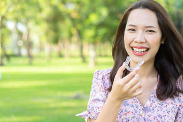 close up young beautiful asian woman smiling with hand holding dental aligner retainer (invisible) at outdoor nature park and garden background for beautiful teeth and dental treatment course concept