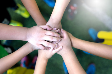 Top view of high five kids hand gesture in junior football team.Boy standing in circle with stack of hands together showing unity.Symbol of celebration or greeting,Success and teamwork Concept.