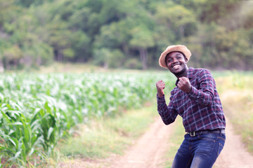 Success african farmer man stand at the green farm with happy and smile.