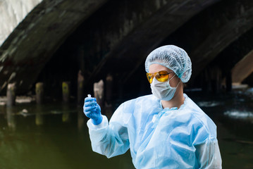 woman ecologist or epidemiologist takes water analysis in city river