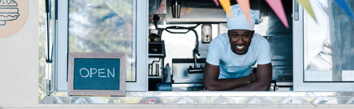 panoramic shot of happy african american man in chef uniform smiling from food truck