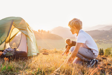 Father and son setting camping tent on the sunset mountain valley at the evening