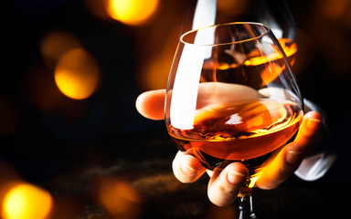 Poster Alcohol French glowing cognac glass in hand on the dark bar counter background, copy space, selective focus