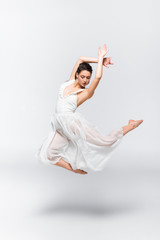 beautiful young ballerina dancing in white dress on grey background