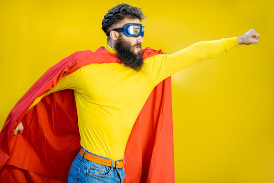 Portrait of a man like a superhero in colorful clothes and pilot's glasses on the yellow background