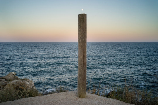 Letter I composed out of a wood pillar and the rising moon over the evening sea ripples.