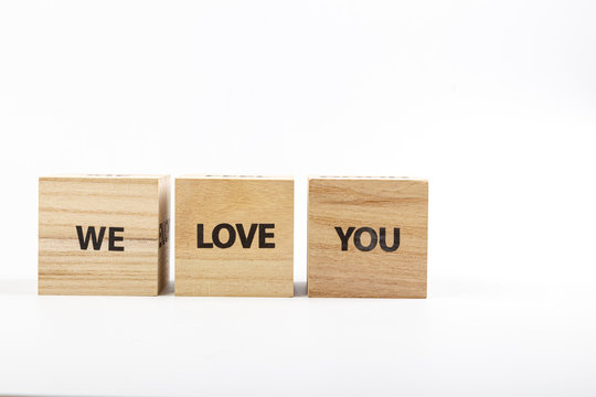 Wooden cubes with the inscriptionWe Love You on a white background