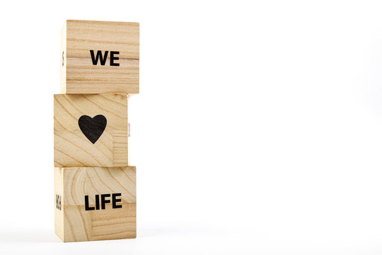 Wooden cubes with the inscription we love life on a white background