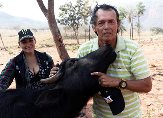 Farmers Ludwing Weber and his wife Viviana pose for a picture with a young buffalo at the Esperanza ranch in the area where wildfires have destroyed hectares of forest near Robore