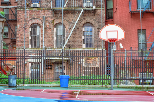Empty basketball court on a rainy day. Surrounded by a fence and between homes. Harlem, NYC, USA.
