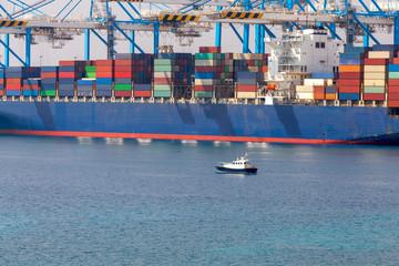 A large container ship is loaded in the cargo port of Malta.