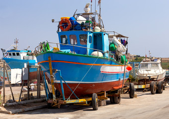 Marsaxlokk. Blue fishing boat on the city promenade.