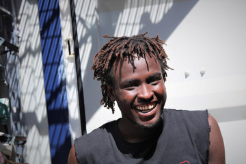 Bob, from Sudan, smiles on the deck of the migrant rescue ship Ocean Viking