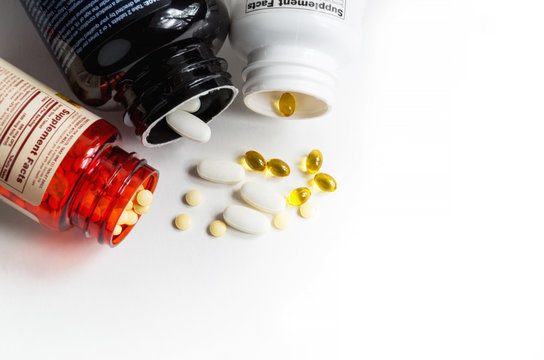 Bottles of magnesium, folic acid and D3 vitamin pills top view