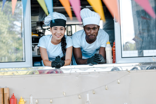 selective focus of asian girl and african american man in hats smiling from food truck