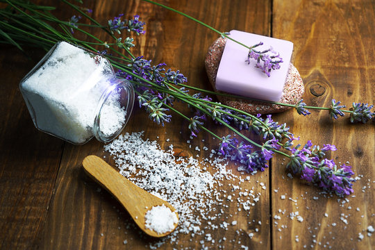 Spa massage setting with lavender flowers, soap and cosmetic salt on wooden background.