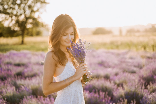 Beautiful Girl Smell Delicate Lavender Bouquet. Caucasian Brunette Woman Hold Bunch of Purple Flower Blossom. Elegant Young Lady in White Sundress Medium Shot. Blooming Meadow Background Bokeh