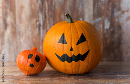 halloween decorations concept - pumpkin and red kuri squash with scary faces on wooden background