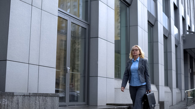 Professional female lawyer walking office building, business woman going work