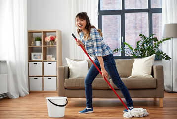 people, housework and housekeeping concept - happy laughing asian woman with mop and bucket cleaning floor and having fun at home