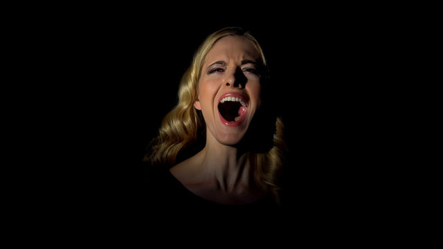 Young woman screaming in dark room, sense of despair, stress and life problems