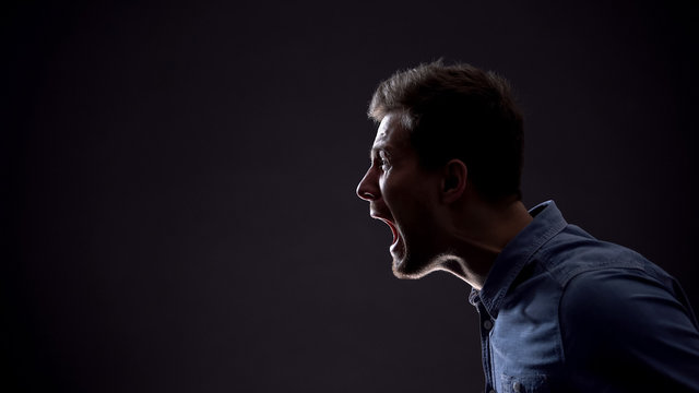 Frustrated man emotionally screaming isolated on black background, life problems
