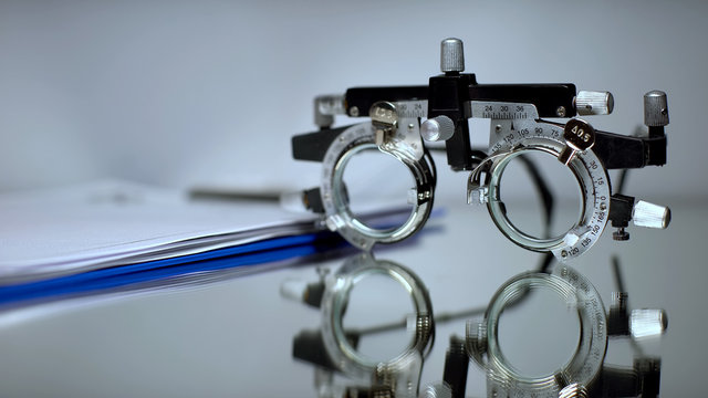 Prescription folder and optical trial frame for vision checking lying on table